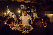 The cook of one of the small restaurants in Omoide Yokocho (or Yakitori Alley) watches proudly as some guests eat the meal he prepared.