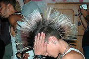 A young punk female with a Mohawk hair cut anf body piercings