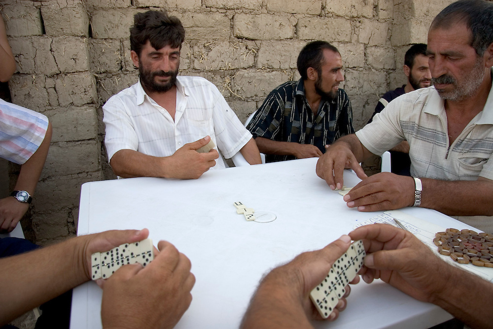 Men in a camp for internally displaced people from Nagorno-Karabakh play dominoes to pass the time because they are unemployed.  The concentration of hundreds of families displaced from their homes, living far from any towns or cities, makes it difficult for most to find adequate employment.  Agdam region, Azerbaijan.