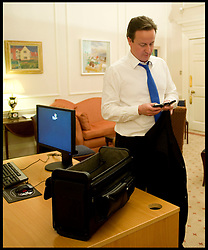 The Prime Minister David Cameron checks his phones in his new office in No10 as Prime Minister on the night he got in. Tuesday May 11 2010, Photo By Andrew Parsons / i-Images