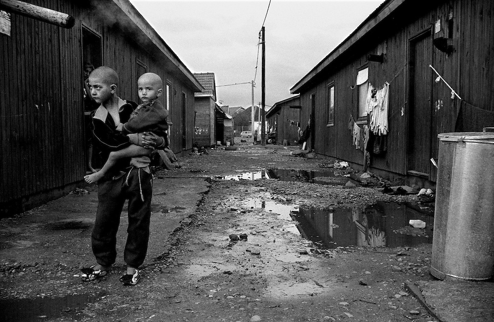 In December 1999 the tents were replaced with barracks in Konik. Each barrack hosts 4 families, each family has 2 rooms, there is no water, no kitchen, but in October 2000 electricity was installed. These 2 girls have had their hair shaved off because of lice. ..Konik camp - a refugee camp for Roma (gypsies) displaced from Kosovo, Montenegro..