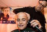 A boy has his head-shaving during the annual St. Baldrick's Day head-shaving fundraiser on Thursday, March 14, 2013, in Arcadia, California. More than100 women and men shaved their heads to raises money for child cancer research. The event, ``St. Baldrick's Day,'' is part of a global effort and the world's biggest volunteer-driven fundraising program for childhood cancer. (Photo by Ringo Chiu/PHOTOFORMULA.com).