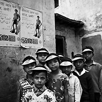 Members of a Bulana Toli (Children's Brigade) from a suburb of Moradabad city dressed in Polio vaccination promotion caps. The Bulana Toli visits households and encourage parents to have their children vaccinated against polio. The scheme is just one of many strategies used by Unicef to identify and challenge those resisting vaccination...India is one of only four countries in the world reported to suffer endemic polio. Only 66 new cases of the disease were reported in India in 2005. But in 2006 that figure leapt ten-fold. In September, UN Secretary General Kofi Annan wrote to Indian Prime Minister Manmohan Singh expressing concern at the new polio outbreak. The Indian government, together with partners including Unicef and Rotary International has embarked on a renewed effort to eradicate polio. Overcrowded areas of poor sanitation are particularly susceptible to the virus. Focusing on the poor north Indian states of Uttar Pradesh and Bihar which between them are home to more than 250 million people, Unicef is coordinating the largest public health drive in the world. The task is to vaccinate all children under the age of five during a series of vaccination rounds. Unicef has mobilised thousands of volunteers to administer and supervise the vaccination effort. Unicef has also recruited people with influence to encourage communities to have their children protected against polio. Misinformation, rumours and a frustration with the lack of other health services mean that many households, particularly in Muslim areas, resist vaccination. ..Photo: Tom Pietrasik.Moradabad, Uttar Pradesh, India..November 12th 2006