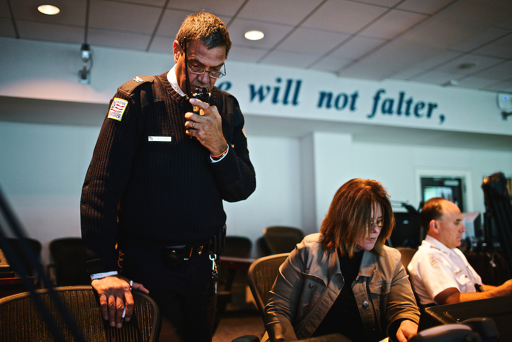 DC police commander Andy Solberg radios officers in his district about a possible man with a gun in a hotel room, while waiting for their morning meeting to begin at the Joint Operation Command Center in Metropolitan Police Station Headquarters in DC.