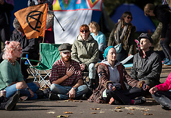 © Licensed to London News Pictures. 09/10/2019. London, UK. Extinction Rebellion activists takes part in a group meditation on Horse Guards Road during a third day of protests in central London. The climate change group intend to blockade the Westminster area for two weeks to demand that the government takes immediate and decisive action on climate change. Photo credit: Peter Macdiarmid/LNP