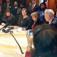 Gov. Michelle Lujan Grisham signs a climate action in her office in the Roundhouse in Santa Fe as members of New Mexico Power and Light, an inter-faith climate activist group, look on. <br /> .