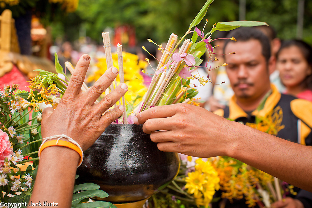 "15 JULY 2011 - PHRA PHUTTHABAT, SARABURI, THAILAND:  People place flowers on a float carrying a robed statue of the Buddha during the Tak Bat Dok Mai at Wat Phra Phutthabat in Saraburi province of Thailand, Friday, July 15. Wat Phra Phutthabat in Phra Phutthabat, Saraburi, Thailand, is famous for the way it marks the beginning of Vassa, the three-month annual retreat observed by Theravada monks and nuns. The temple is highly revered in Thailand because it houses a footstep of the Buddha. On the first day of Vassa (or Buddhist Lent) people come to the temple to ""make merit"" and present the monks there with dancing lady ginger flowers, which only bloom in the weeks leading up Vassa. They also present monks with candles and wash their feet. During Vassa, monks and nuns remain inside monasteries and temple grounds, devoting their time to intensive meditation and study. Laypeople support the monastic sangha by bringing food, candles and other offerings to temples. Laypeople also often observe Vassa by giving up something, such as smoking or eating meat. For this reason, westerners sometimes call Vassa the ""Buddhist Lent."" The tradition of Vassa began during the life of the Buddha. Most of the time, the first Buddhist monks who followed the Buddha did not stay in one place, but walked from village to village to teach. They begged for their food and often slept outdoors, sheltered only by trees. But during India's summer rainy season living as homeless ascetics became difficult. So, groups of monks would find a place to stay together until the rain stopped, forming a temporary community. Wealthy laypeople sometimes sheltered monks on their estates. Eventually a few of these patrons built permanent houses for monks, which amounted to an early form of monastery. Photo by Jack Kurtz / ZUMA Press  PHOTO BY JACK KURTZ"