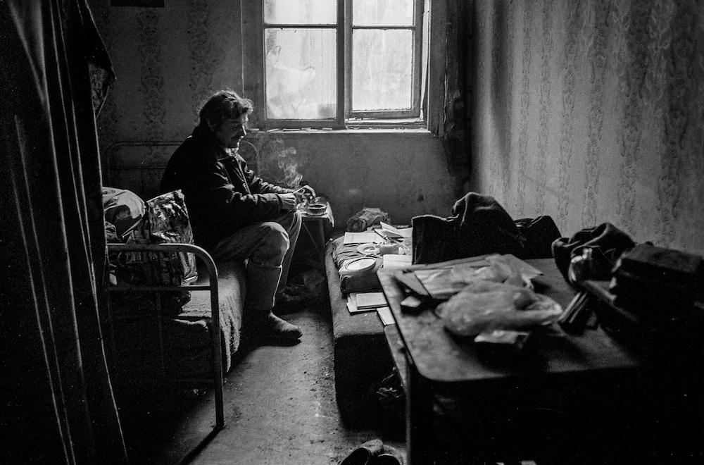 Man having a cigarette in his room somewhere in Zizkov.