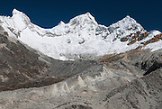 The summits of Huandoy Sur (South) 6,160m (left), Huandoy Oeste (West) 6,356m & Huandoy Norte (North) 6,395m (centre) and Huandoy Este (East) 6,068m (right).  Viewed from the trail between Pisco Base Camp and Laguna 69, at approx. 5,000m.  The refugio at Pisco Base Camp is visible lower centre left, beyond the foreground moraines. Huascarán National Park, Cordillera Blanca, Peru.  Nikon D200, 17-50/2.8.