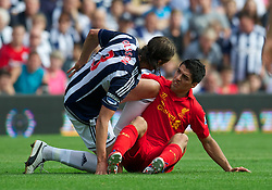WEST BROMWICH, ENGLAND - Saturday, August 18, 2012: Liverpool's Luis Alberto Suarez Diaz is fouled by West Bromwich Albion's Jonas Olsson during the opening Premiership match of the season at the Hawthorns. (Pic by David Rawcliffe/Propaganda)