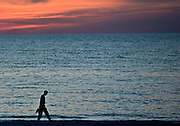 Man takes sunset stroll at Anna Maria Island, Florida, United States of America