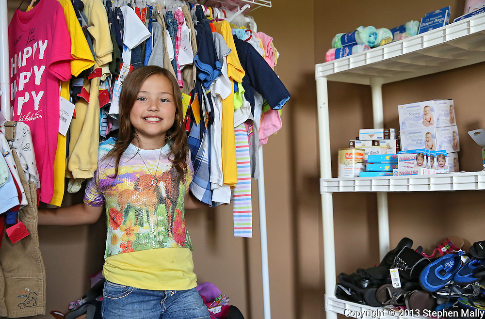 """Raegan Junge, 8, of Keystone stands by a rack of clothes and a shelf of supplies ready to send out to families in need in her """"office"""" at her house in Keystone on Wednesday, July 17, 2013."""