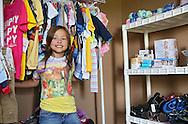 "Raegan Junge, 8, of Keystone stands by a rack of clothes and a shelf of supplies ready to send out to families in need in her ""office"" at her house in Keystone on Wednesday, July 17, 2013."
