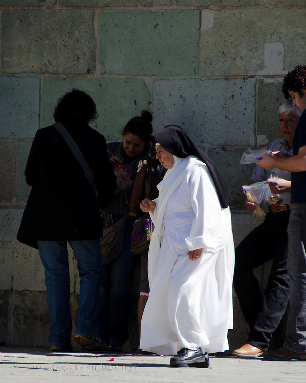 A Dominican nun walks past the Catedral de Oaxaca.