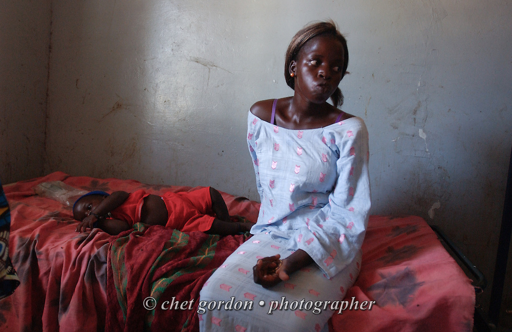 Senegalese mother sits with her child infected with malaria in the Medical Center of Diossong, Senegal on Tuesday, October 31, 2006.