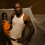 Arouna Ouedraogo (44) and his son, Kader Ouedraogo (4), with a mosquito net in the village of Songodin in the Sanmatenga region of Burkina Faso on 25 February 2014. Mosquito nets greatly decrease the incidence of malaria by reducing the risk of being bitten by the nocturnal Anopheles mosquito, which carries the malaria parasite.