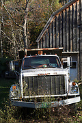 Old GMC truck by traditional and typical old barn in Vermont, New England, USA