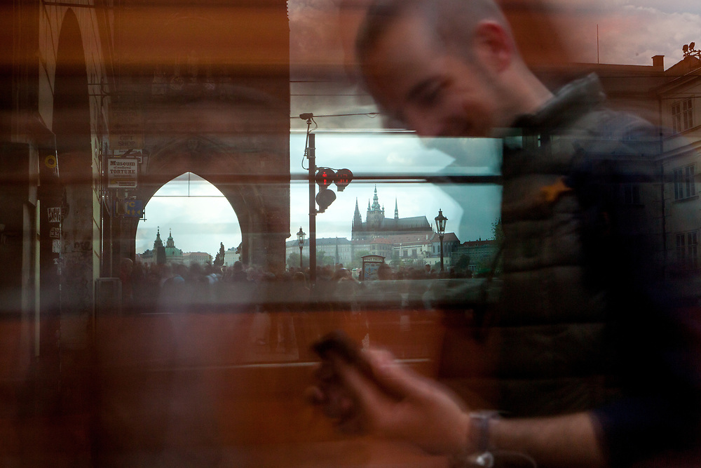 "A man sitting in a tram looking at his mobile device. In the back a crowd moving from the beginning of Charles Bridge towards ""Lesser Town"" (Mala Strana) and Prague Castle."