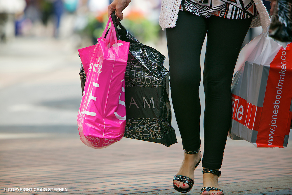 Close up of woman carrying lots of shopping carrier bags.jpg ...