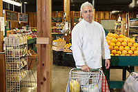 Portrait of a mid adult chef with shopping cart in farmer's market