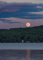 The full moon rises over Meredith Bay on Tuesday evening.  (Karen Bobotas/for the Laconia Daily Sun)