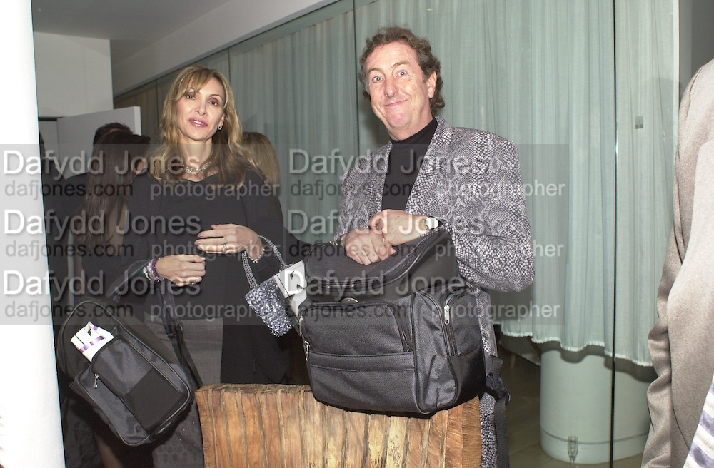 Mr. & Mrs. Eric Idle with gift bags leaving the Talk pre-globe Awards Party. Mondrian, Los Angeles. 22/1/2000. <br />© Copyright Photograph by Dafydd Jones 66 Stockwell Park Rd. London SW9 0DA Tel 0171 733 0108 www.dafjones.com