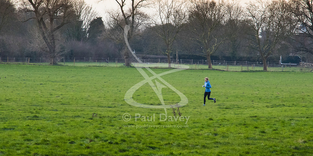 Richmond, London, February 17th 2016. A woman jogs across the fields as dawn breaks over  Richmond. <br /> ///FOR LICENCING CONTACT: paul@pauldaveycreative.co.uk TEL:+44 (0) 7966 016 296 or +44 (0) 20 8969 6875. ©2015 Paul R Davey. All rights reserved.