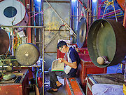 """26 NOVEMBER 2014 - BANGKOK, THAILAND: A musician goes over his sheet music before playing at a Chinese opera at the Chow Su Kong Shrine in the Talat Noi neighborhood of Bangkok. Chinese opera was once very popular in Thailand, where it is called """"Ngiew."""" It is usually performed in the Teochew language. Millions of Chinese emigrated to Thailand (then Siam) in the 18th and 19th centuries and brought their culture with them. Recently the popularity of ngiew has faded as people turn to performances of opera on DVD or movies. There are about 30 Chinese opera troupes left in Bangkok and its environs. They are especially busy during Chinese New Year and Chinese holidays when they travel from Chinese temple to Chinese temple performing on stages they put up in streets near the temple, sometimes sleeping on hammocks they sling under their stage.      PHOTO BY JACK KURTZ"""