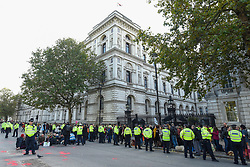 © Licensed to London News Pictures. 18/10/2019. LONDON, UK.  Police prepare to arrest climate activists from Extinction Rebellion who are protesting outside Downing Street.  The red hand prints symbolise blood on their hands. Activists are calling on the government to take immediate action on the negative effects of climate change.  Photo credit: Stephen Chung/LNP