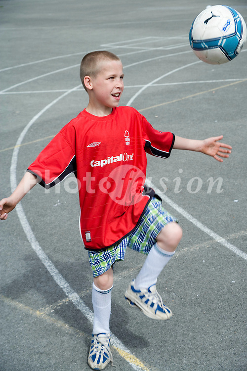 Young boy playing with football in school playground,
