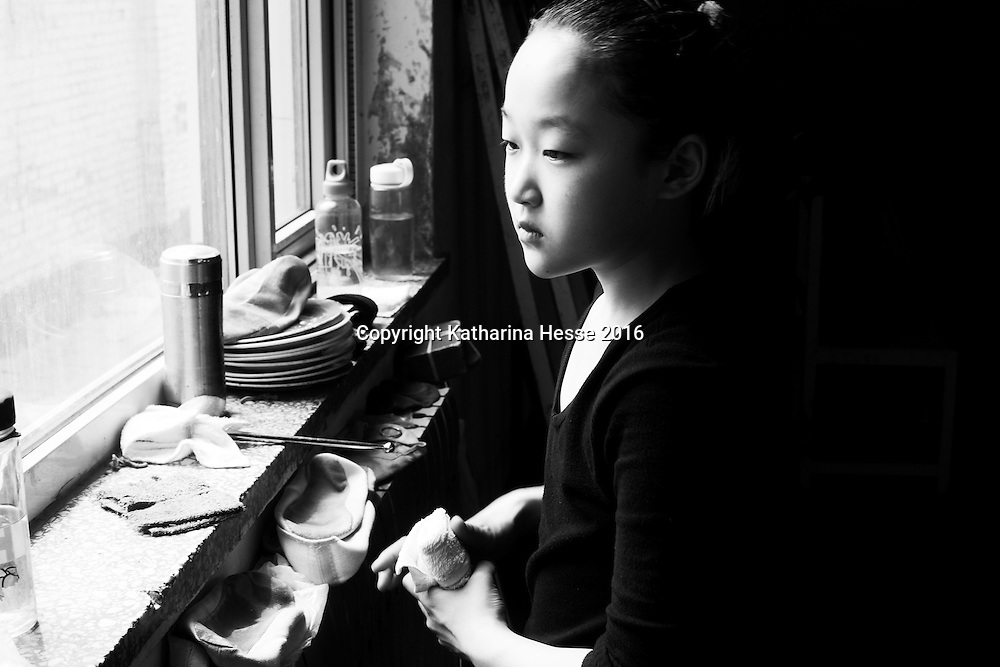 Wuqiao, April 20, 2016 : a young apprentee looks out of a window after the daily training in an acrobats school in Wuqiao.<br /> Acrobatic performances belong to Chinas variety arts and have existed for centuries. Acrobats originally were to entertain poor villagers in the countryside. Nowadays it's a profession for young people from the countryside seeking a better life in China's big cities where they lead a life as outcasts. Their monthly income is not enough to participate in social life , let alone to have private lifes. The troupes often live together in basic housing such as dorms and it's difficult to break out.
