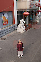 Qi Shizhen photographed in front of the restaurant which has now replaced the house where she lived in October 1949.