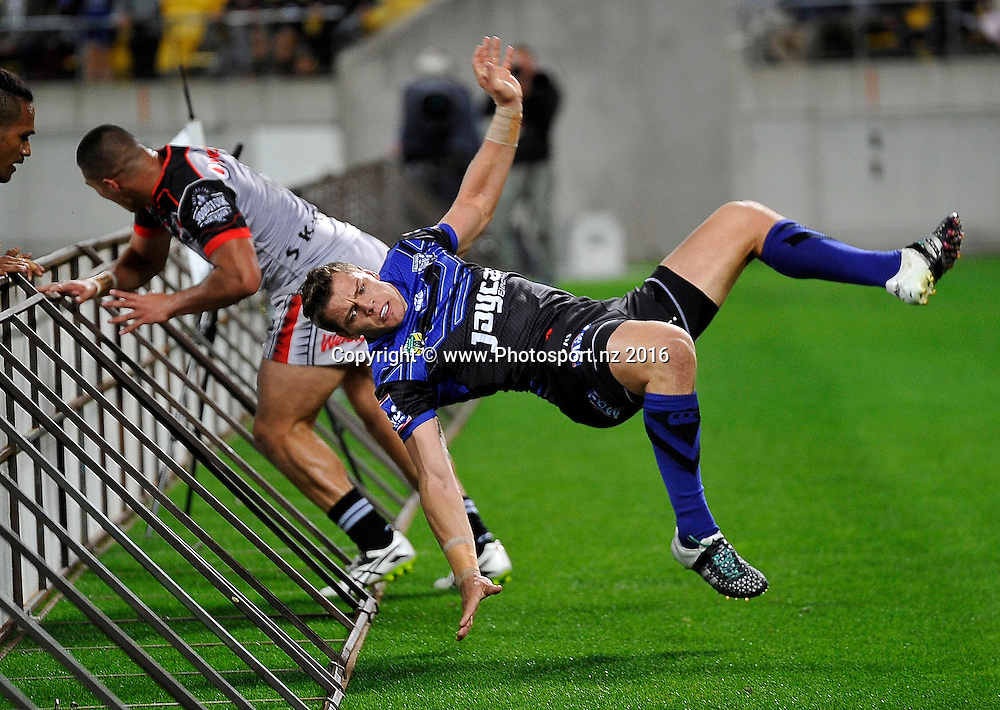 Bulldogs' Kerrod Holland (R leaps the fence with Warriors' Tuimoala Lolohea during the NRL Warriors vs Bulldogs Rugby League match at the Westpac Stadium in Wellington on Saturday the 16th of April 2016. Copyright Photo by Marty Melville / www.Photosport.nz
