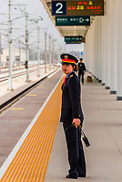 A female train conductor awaits the arrival of a train at Liuyan Nan Railway station, which services high speed trains to Beijing, Xi'an, Chengdu and Urumqi. It is 130 km. from Dunhuang in Gansu Province, China.