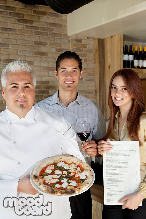 Portrait of happy chef holding pizza with young couple