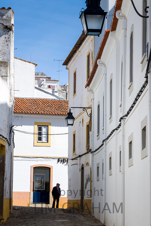 Old man in typical street scene of white and yellow houses, lanterns and narrow cobble street in Evora, Portugal