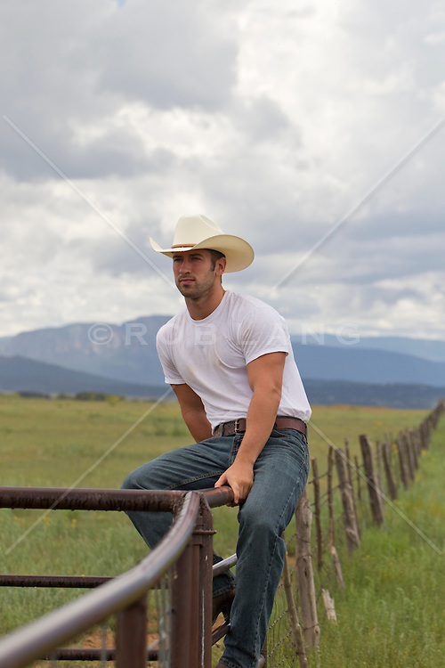 Cowboy sitting on a fence in New Mexico