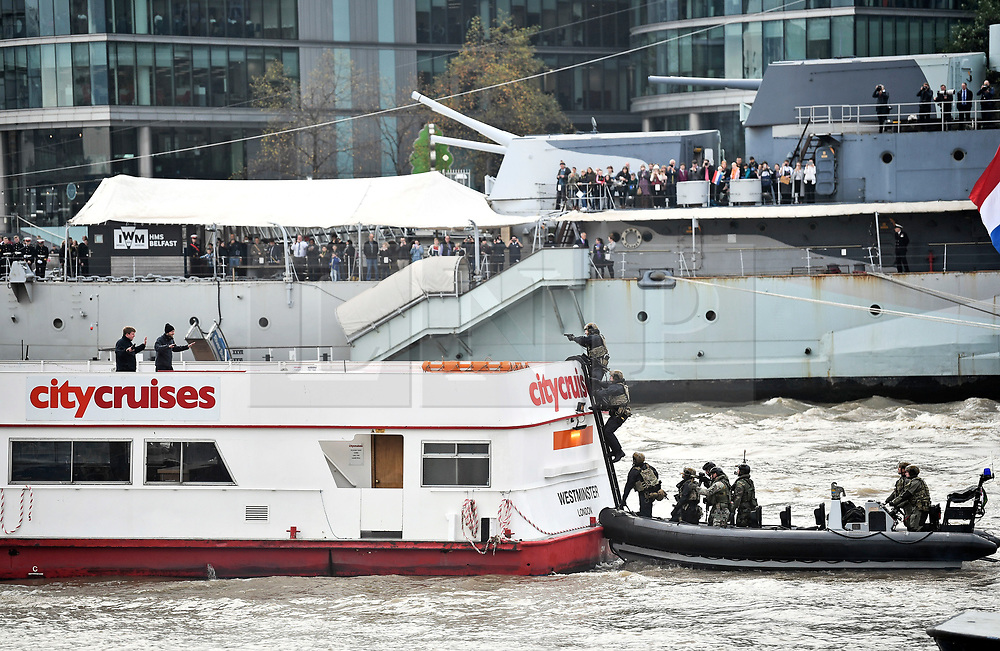 © Licensed to London News Pictures. 24/10/2018. London, UK. Hostages hold up their hands as armed Marines board a City Cruises boat ferry taken by hostages during the exercise. British Royal Marines are joined by the The Royal Netherlands Marines in a military demonstration at HNLMS Zeeland, which is anchored next to anchored next to HMS Belfast on the River Thames in central London. Members of the British and Dutch Royal families watched the event as part of a state visit to the UK. Photo credit: Ben Cawthra/LNP