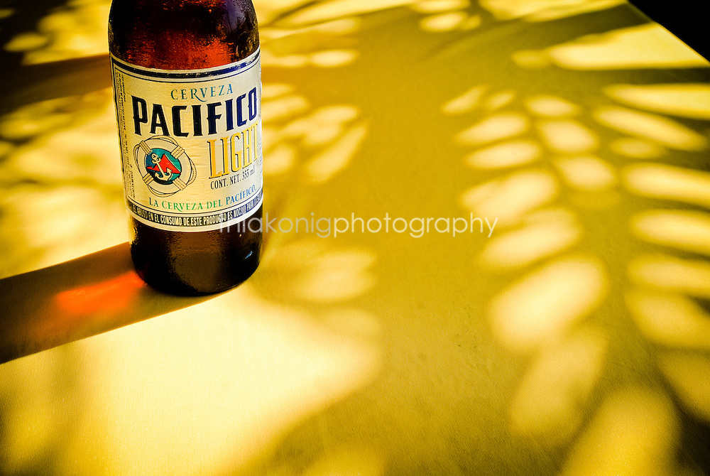 A Pacifica beer on a yellow table cloth with shadow of palm tree, San Blass, Mexico