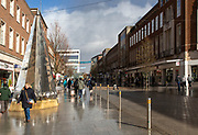 Wet pavements sunshine after rain show High Street, Exeter, Devon, England, UK