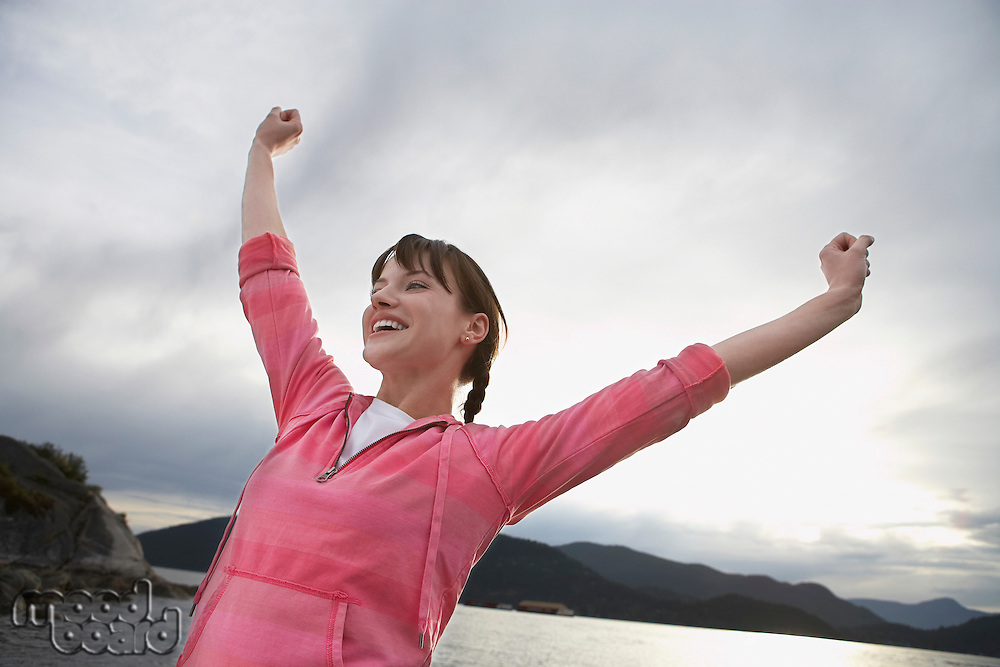 Woman with arms raised at ocean