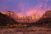 The desert sky erupts in a blaze of color over the Towers of Virgin in Zion National Park.