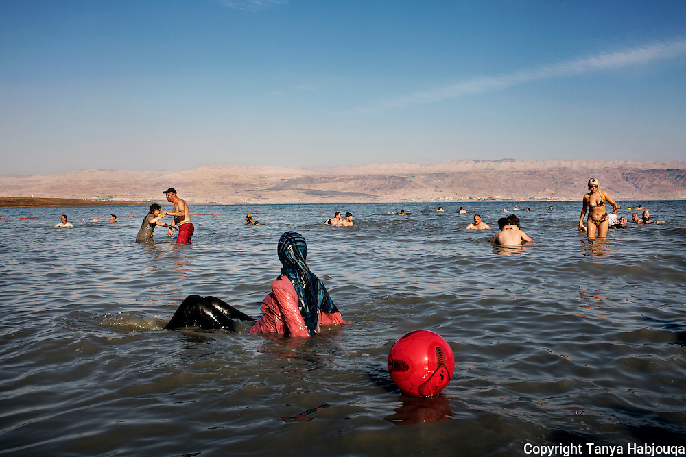 A Palestinian woman enjoying a day at the dead sea looks across to the Jordan side. (west bank)