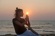 Woman doing yoga on the beach at sunset in Bekal, Kerala, India.