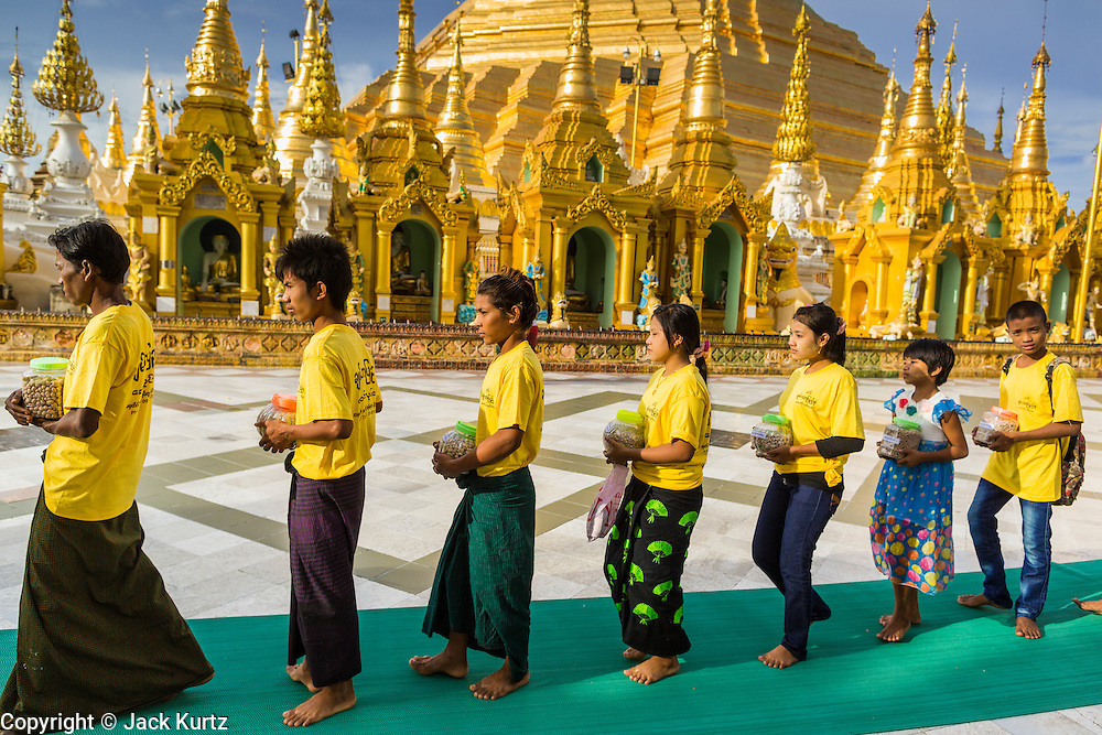 07 JUNE 2014 - YANGON, YANGON REGION, MYANMAR: Children participate in a small private procession during a merit making ceremony for their parents' company at Shwedagon Pagoda in Yangon. Shwedagon Pagoda is officially called Shwedagon Zedi Daw and is also known as the Great Dagon Pagoda and the Golden Pagoda. It's a 99 metres (325ft) gilded pagoda and stupa located in Yangon. It is the most sacred Buddhist pagoda in Myanmar with relics of the past four Buddhas enshrined within: the staff of Kakusandha, the water filter of Koṇāgamana, a piece of the robe of Kassapa and eight strands of hair from Gautama, the historical Buddha.   PHOTO BY JACK KURTZ