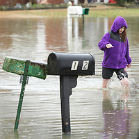 Luci Eickford, 10, of Saltillo, walks through the flood waters on Maplewood Drive in the Willow Creek subdivision