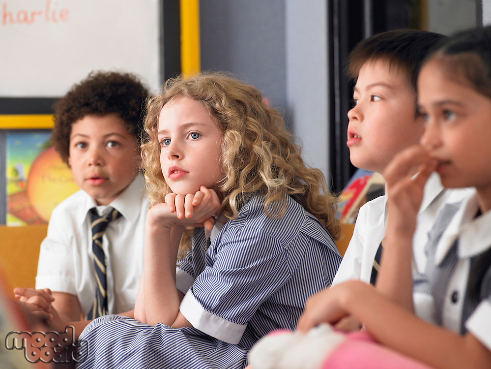 Elementary students sitting in row in classroom