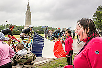 July 8, 2015, Ablain-Saint-Nazaire — People are braving the bad weather to cheer on the cyclists at stage five of the Tour de France, which passes many memorial sites of the First World War. In the background stands the lighthouse-ossuary of Notre-Dame-de-Lorette, one of the largest French military cemetery that holds the remains of more than 40,000 soldiers.