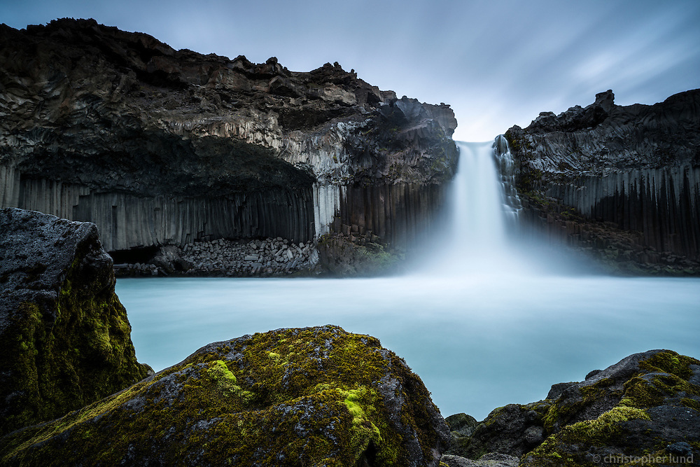 The Aldeyjarfoss waterfall is situated in the north of Iceland at the northern part of the Sprengisandur Highland Road which means it is to be found within the Highlands of Iceland. One of the most interesting features of the waterfall is the contrast between the black basalt columns and the white waters of the fall. The river Skjálfandafljót drops here from a height of 20 m. The basalt belongs to a lava field called Frambruni or Suðurárhraun, hraun being the Icelandic designation for lava.