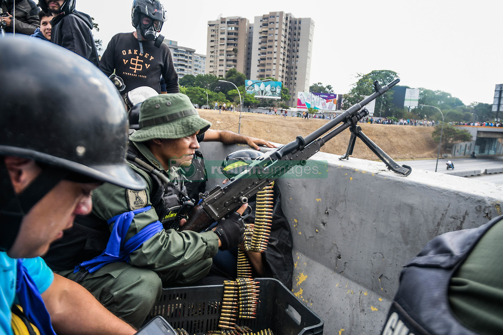 April 30, 2019 - Caracas, Miranda, Venezuela - An anti government solider seen with his machine gun taken up position ready for battle..Venezuelan military who are supporting the Venezuelan opposition leader Juan Guaido took to the street with their weapons together with anti government protesters in a military coup against the socialist government lead by President Nicolas Maduro. (Credit Image: © Roman Camacho/SOPA Images via ZUMA Wire)